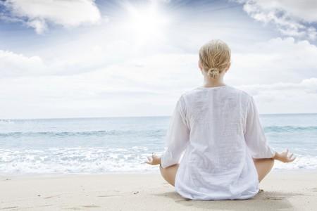 海辺で瞑想している女性の後ろ姿