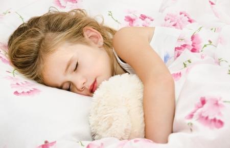 ぬいぐるみを抱いて眠る子ども