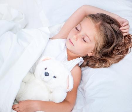 クマのぬいぐるみと眠る少女