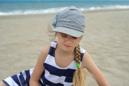 砂浜にすわる幼い子ども。