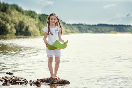 川で船を浮かべて遊ぶ子ども