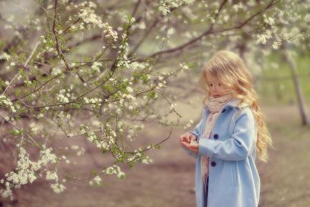春の公園で木の下にいる少女