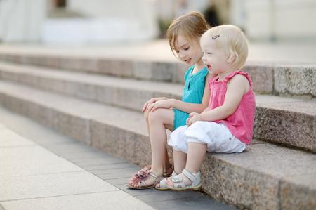 階段に腰掛けている幼い子どもたち