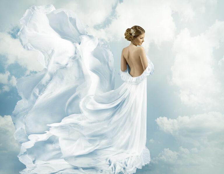 雲が浮かぶ空を背景とした女性の姿