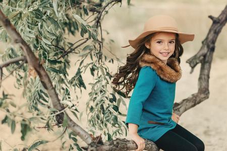 木の枝に腰掛ける少女
