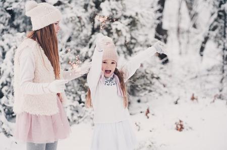 雪の中で花火をする姉妹