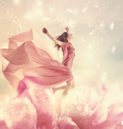 牡丹の花の上でジャンプする女性