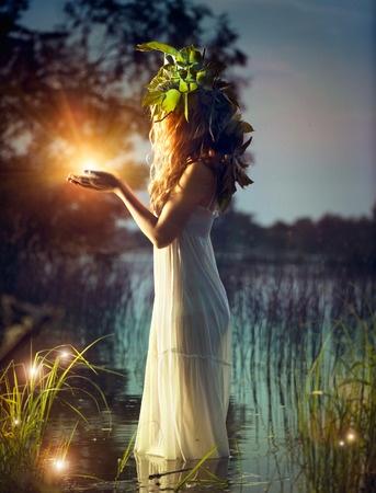 夜の池で光を手にする女性