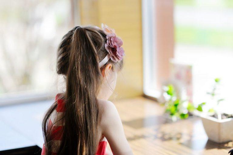 窓辺で考える子どもの後ろ姿