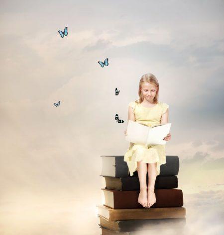 本を重ねた上に腰掛ける少女