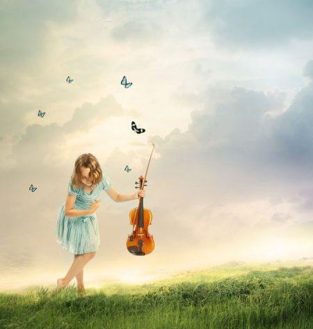 草原でバイオリンを手にする少女