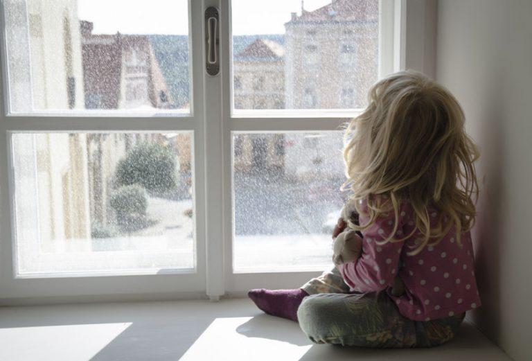 窓の外をみつめる子供