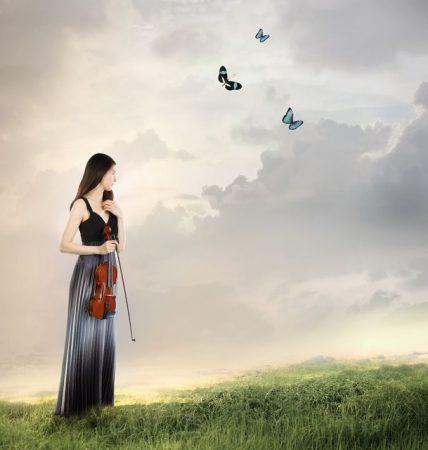草原にバイオリンをもつ女性