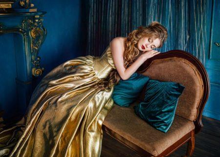 ソファーで目を閉じ考える美女