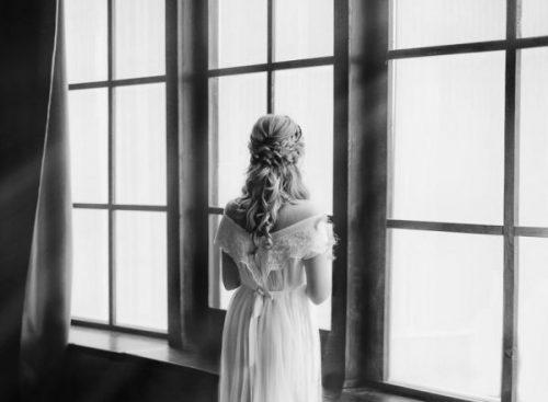 窓にたたずむ女性の後ろ姿